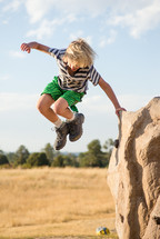 a boy child jumping outdoors