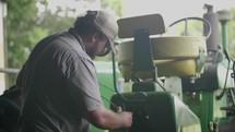 a farmer fixing a tractor