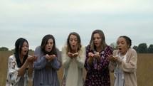 women blowing confetti in a field
