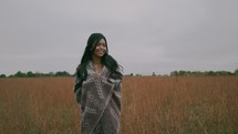 a woman walking through a field outdoors