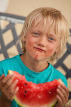 boy child eating a watermelon on a summer day