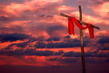 red tunic hanging on a wood cross against a fiery sky at sunset