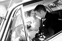 bride and groom sitting in their car