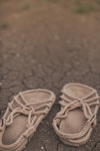 Rope sandals on the dry, cracked earth.