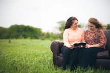 Smiling mother and daughter reading the Bible together while sitting on a sofa in a field.