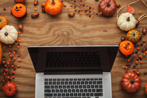 laptop computer surrounded by fall decorations
