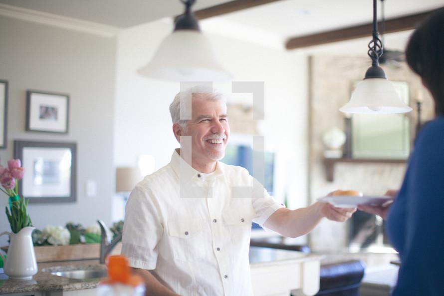 woman serving a man a donut