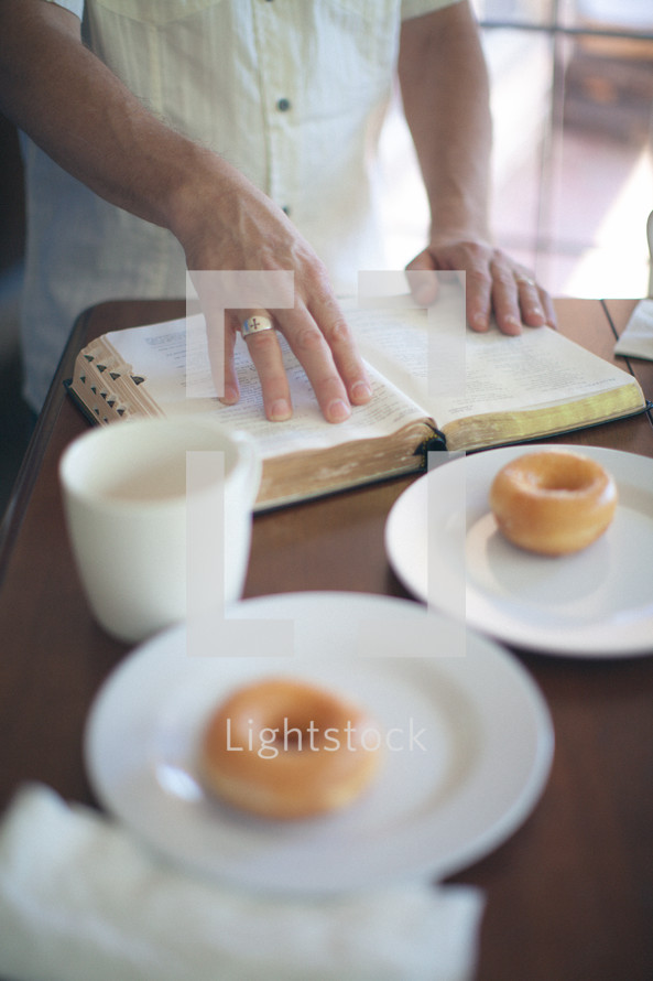 Man's hands on an open Bible at the breakfast table.