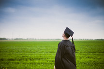 Graduate standing in a field of greeen grass looking up.