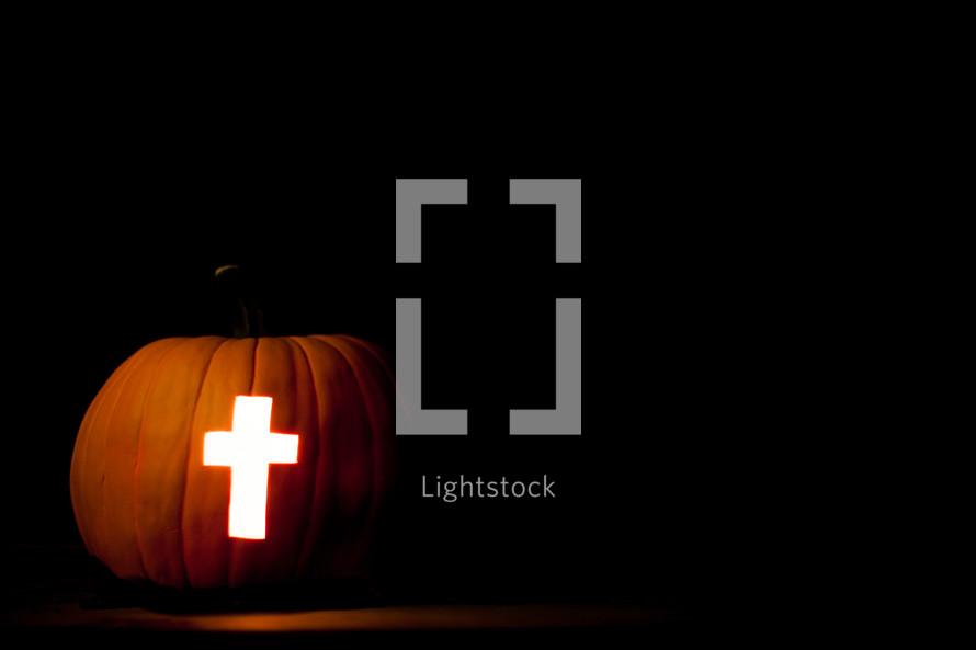 cross carved in a Jack-O-Lantern pumpkin