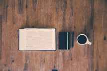 open Bible, journal, pen, and coffee mug on a wood floor