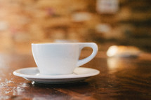 A white cup and saucer on a wooden table.