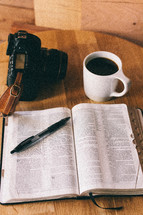 An open Bible, cup of coffee, and a camera on a table.