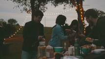 people gathered around a table getting food