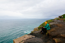 a woman in a raincoat sitting on a shore on the Cliffs of Moher