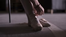 ballerina tying her toe shoes