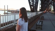 girl looking over a railing on a bridge