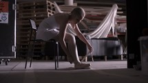 ballerina tying her toe shoes