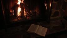 open Bible near a fire in a hearth