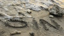 word sin in sand washed away by the ocean