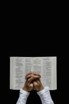 man praying over an open Bible