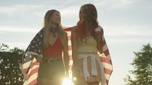 young women walking with an American flag draped over their backs