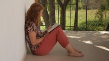 Woman sitting outside, leaning against a wall, reading a book.