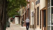 a man walking down a sidewalk downtown