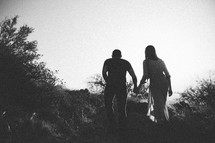Silhouette of a couple walking up a hill.