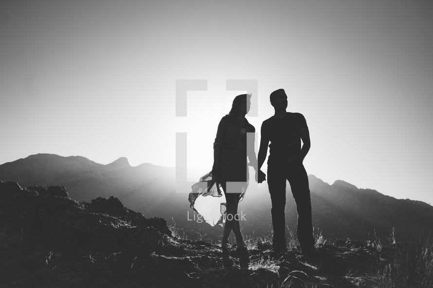 Silhouette of a couple holding hands while standing on a mountain.