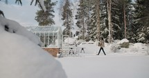 a woman carrying plants in to a greenhouse in the snow