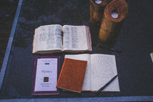 Open bible with the Book of Hosea and a journal on a glass table with candles.