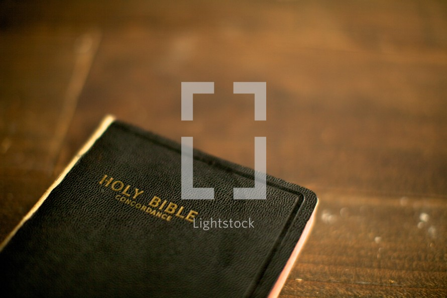 A Holy Bible resting on a wood table