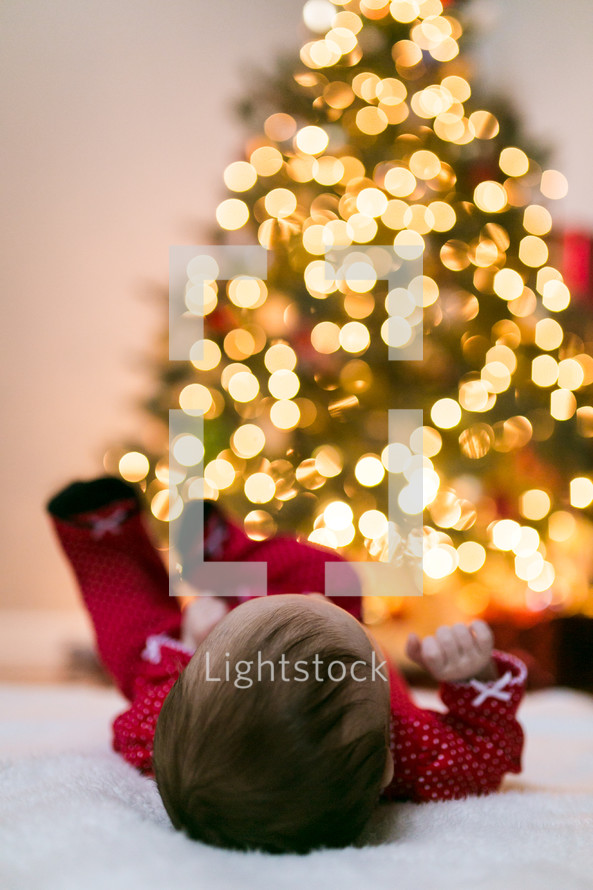 baby lying under Christmas tree