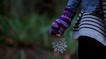 woman walking outdoors holding a snowflake ornament