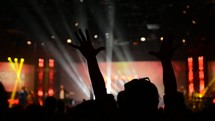 waving raised hands in worship under spot lights