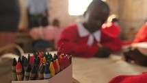 children coloring with crayons in a schoolhouse in Africa