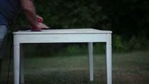 a man sanding a table