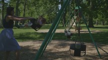 a mother pushing her daughter on a swing