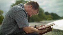 a man sitting on a beach reading a Bible and praying