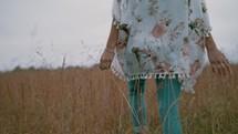 a woman walking through a field of tall grasses