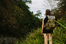 a woman backpacking in a forest