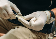 a doctor threading a needle for stitches
