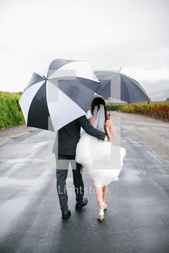 bride and groom walking carrying umbrellas
