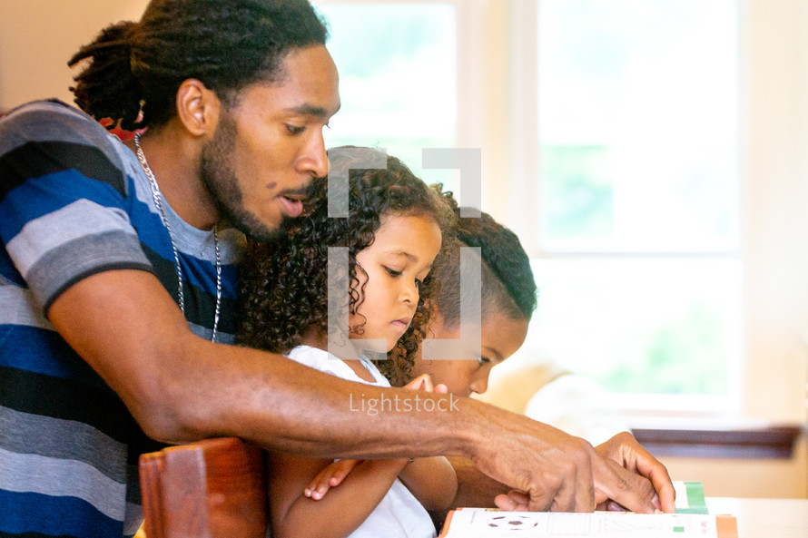 a father helping his kids do homework
