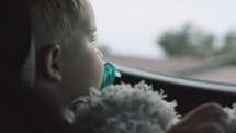toddler in a carseat looking out a car window
