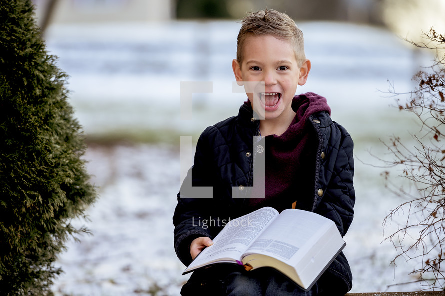 boy child holding a Bible standing outdoors in snow