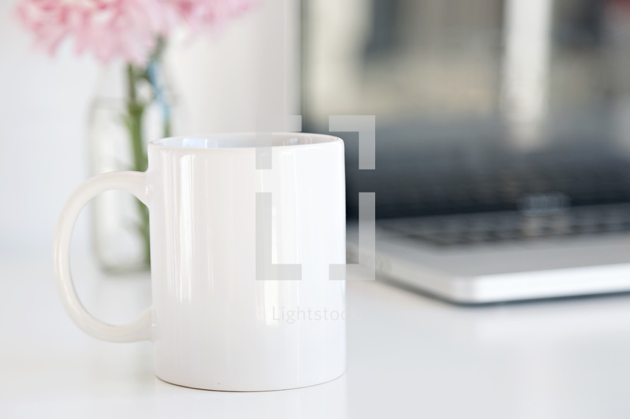 coffee cup, laptop computer, and vase of flowers on a desk