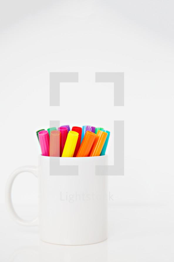 white mug full of markers