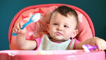 messy face of a toddler girl eating with a spoon in a highchair